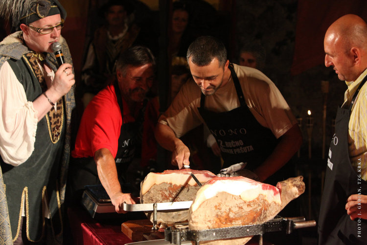 Slicing smoked ham at Krk Fair Lovrečeva